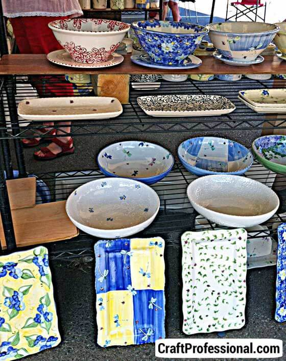 Delicate pottery displayed on wire racks.