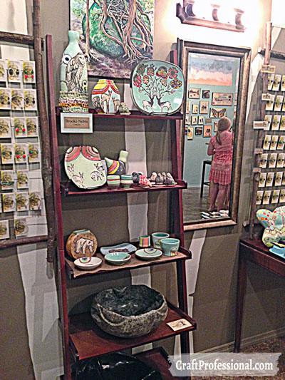 Handmade pottery displayed on a ladder shelf in a retail shop.