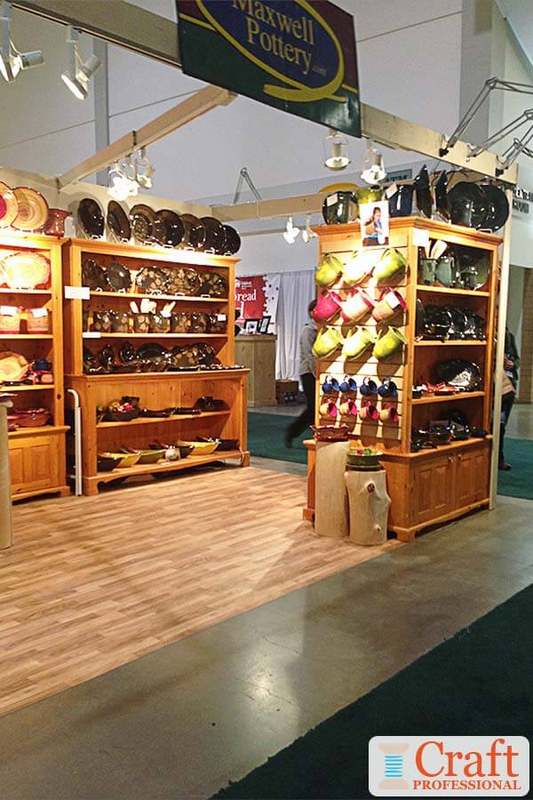 Traditional handmade tableware displayed on substantial wooden shelves at an indoor craft fair.