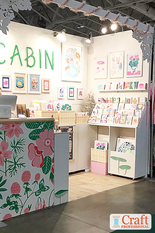Art prints and cards on display at a craft show in a bright pink, green, and white booth.