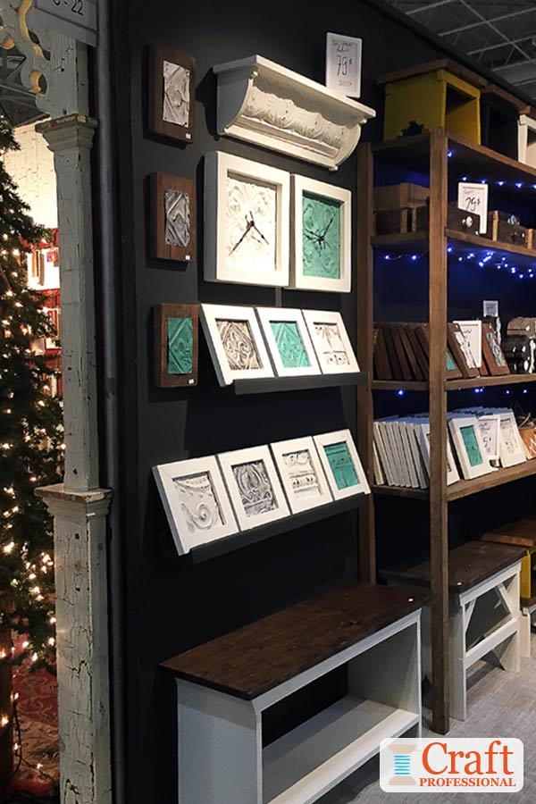 Handmade clocks displayed against a black backdrop at a craft show.