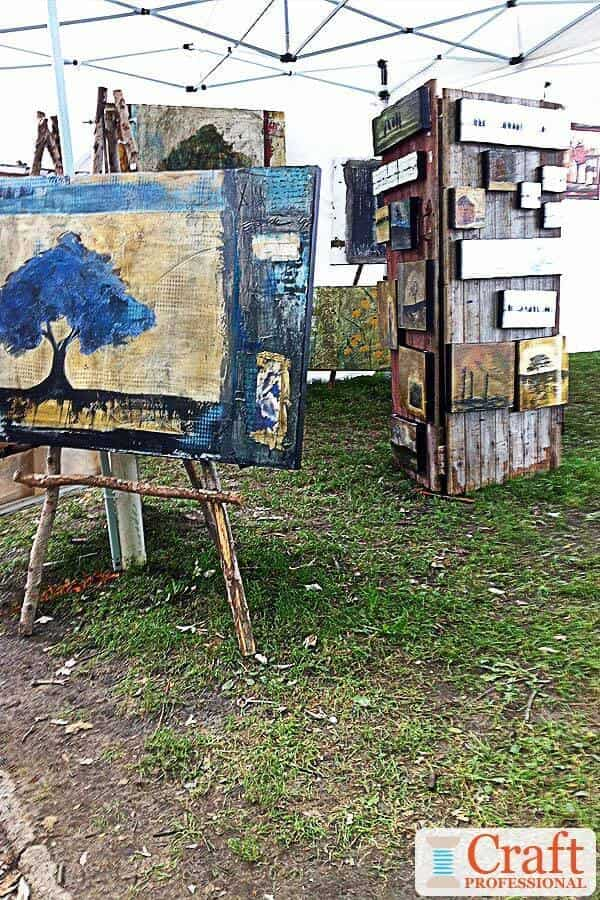 Paintings displayed at an outdoor craft show on DIY wood easels.