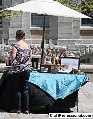 Irregular shaped outdoor craft booth under white market umbrella.